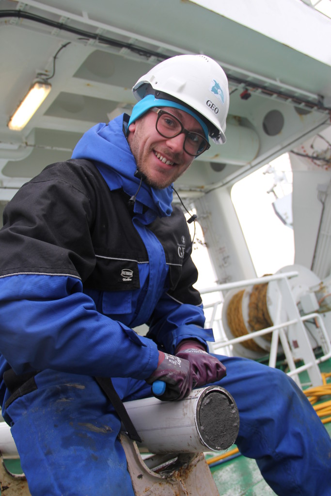 A modeller with clay on his hands! Mads Bruun  Poulsen from NBI cutting a 20 m long sediment core into sections. The  core was taken earlier this week, south of Scoresby Sund, Greenland.  Photo: Ida Synnøve Olsen